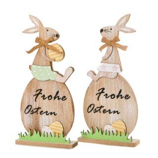 putziger großer Osterhase auf Ei mit Schriftzug Frohe Ostern als Hasenjunge oder Hasenmädchen